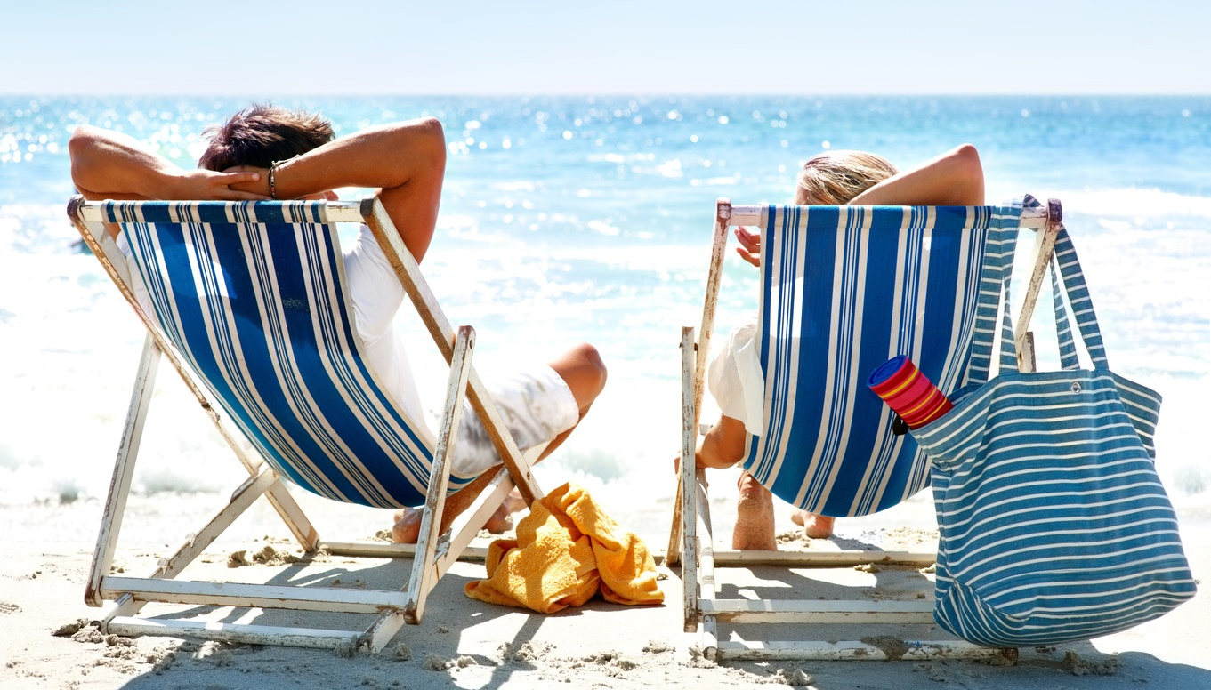 Couple on a deck chair relaxing on the beach